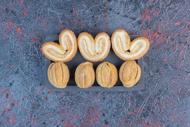 Biscoitos em flocos e bolinhos de biscoito recheados com caramelo em uma pequena bandeja na mesa abstrata.