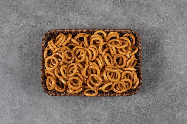 Biscoitos em forma de anel dentro da cesta sobre superfície cinza.