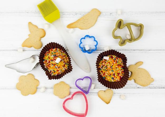 Biscoitos em forma de animais com utensílios de cozinha na mesa branca