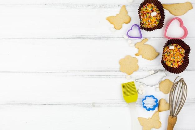 Biscoitos em forma de animais com utensílios de cozinha na mesa de madeira