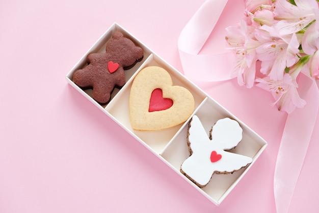 Biscoitos em forma de anjo, coração, urso com uma fita rosa com lisianthuses
