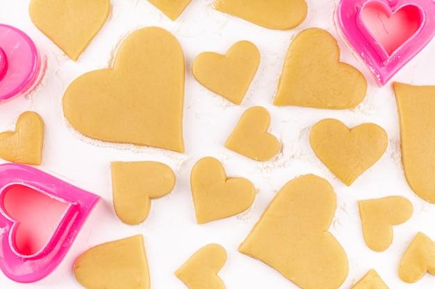 Biscoitos em forma de coração caseiro cru com cortador de biscoitos rosa e farinha