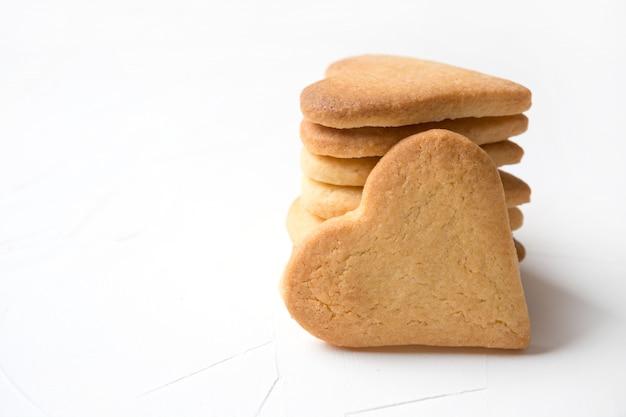Biscoitos em forma de coração caseiro na mesa branca.