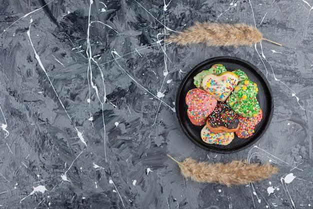 Biscoitos em forma de coração com granulado colorido e uma xícara de chá preto.