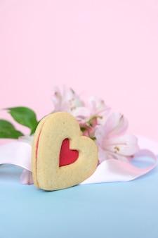 Biscoitos em forma de coração com uma fita rosa em um fundo rosa com lisianthuses
