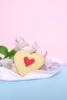 Biscoitos em forma de coração com uma fita rosa em um rosa