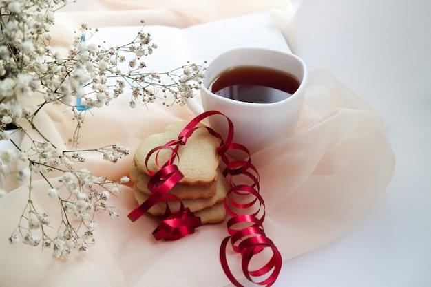 Biscoitos em forma de coração com uma fita vermelha e um buquê de flores branco. espaço para texto.