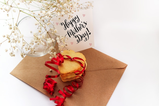 Biscoitos em forma de coração com uma fita vermelha e um buquê de flores branco.