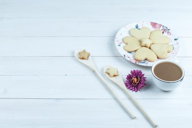 Biscoitos em forma de coração de vista de alto ângulo, xícara de café com flor, biscoitos estrela em colheres de madeira no fundo branco da placa de madeira. horizontal