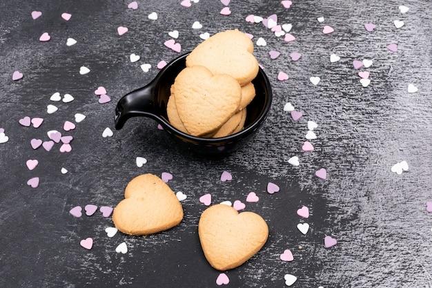 Biscoitos em forma de coração de vista superior na superfície escura