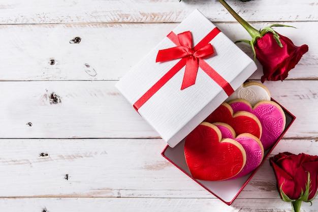 Biscoitos em forma de coração e rosas para dia dos namorados na mesa de madeira branca, espaço de cópia