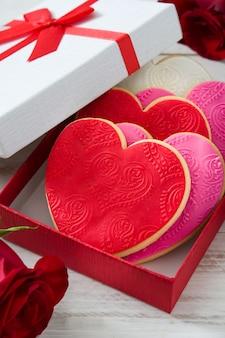 Biscoitos em forma de coração em caixa de presente decorada com rosas para dia dos namorados na mesa de madeira branca