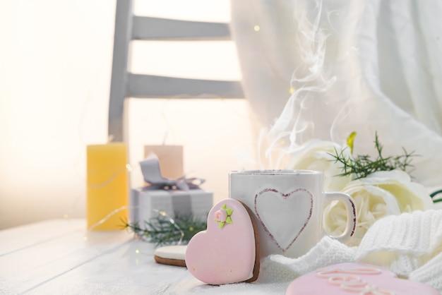 Biscoitos em forma de coração festivo com vidros coloridos e xícara de café em uma mesa de madeira com espaço de cópia para comemorar o dia dos namorados, aniversário ou casamento