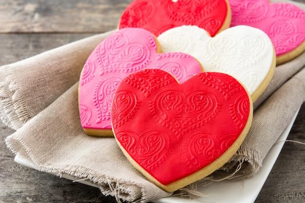 Biscoitos em forma de coração para dia dos namorados na mesa de madeira fechar