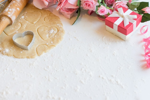Biscoitos em forma de coração para o dia dos namorados, flores rosas e caixa de presente rosa em fundo branco de madeira, copie o espaço