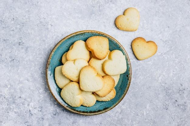 Biscoitos em forma de coração para o dia dos namorados na placa azul. vista do topo. postura plana. copie o espaço