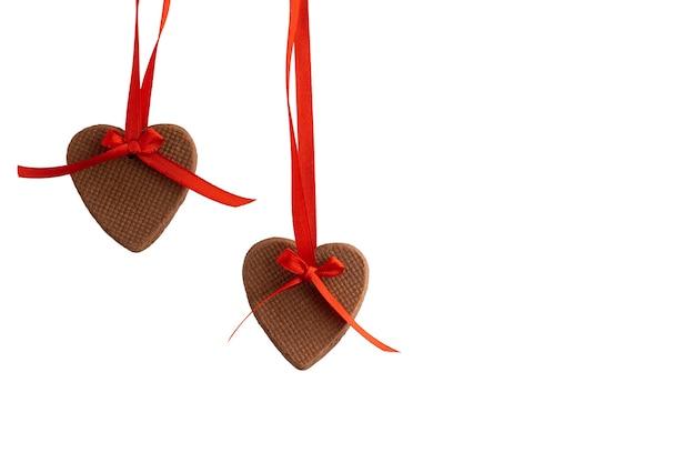 Biscoitos em forma de coração pendurados na fita vermelha sobre fundo branco. decoração de dia dos namorados. isolar