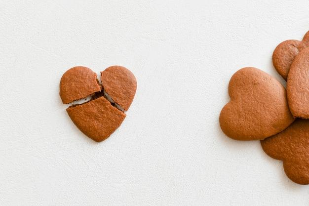 Biscoitos em forma de coração, um deles é quebrado em um fundo branco.