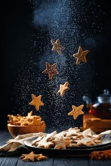 Biscoitos em forma de estrela caindo com açúcar em pó