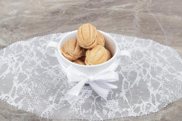 Biscoitos em forma de noz em uma tigela branca.