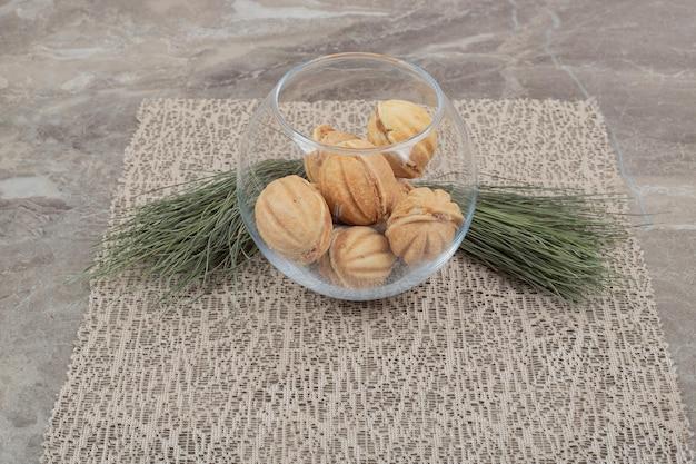 Biscoitos em forma de noz em uma tigela de vidro na serapilheira.