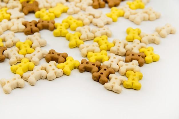 Biscoitos em forma de osso para cães ossos multicoloridos de biscoitos isolados em um fundo branco