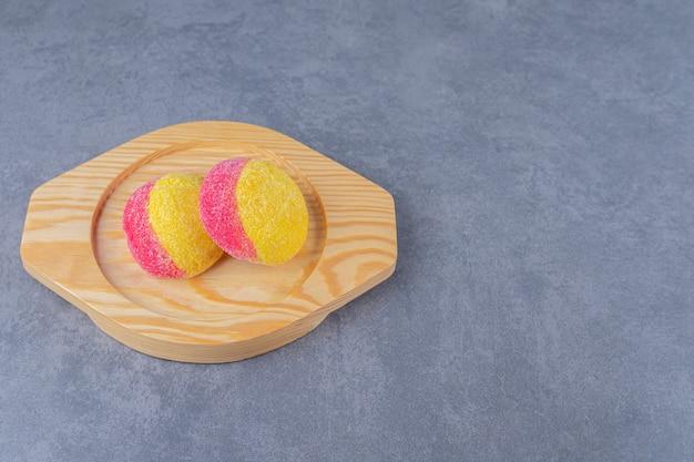 Biscoitos em forma de pêssegos em uma placa de madeira na mesa de mármore.