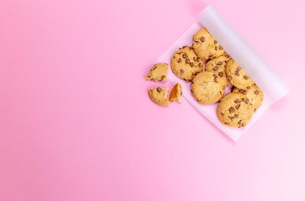 Biscoitos em papel pergaminho em fundo rosa