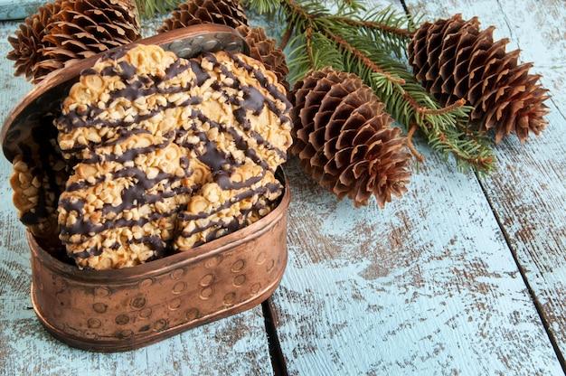 Biscoitos em ramos de caixa de cobre e árvore de natal