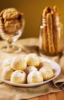 Biscoitos em tons de bege em um guardanapo em um prato e em uma jarra.