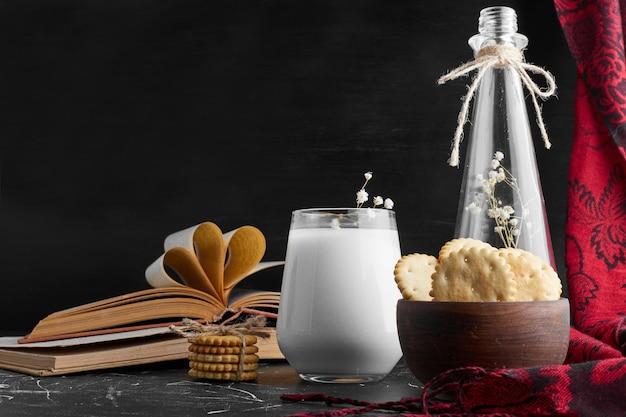 Biscoitos em um copo de madeira com um copo de leite.