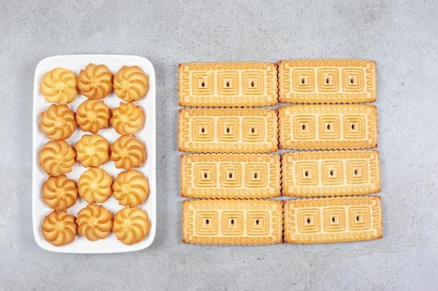 Biscoitos em um prato ao lado de biscoitos bem alinhados em fundo de mármore. foto de alta qualidade