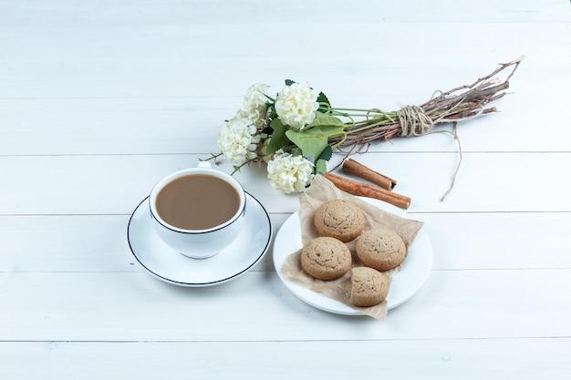 Biscoitos em um prato branco com uma xícara de café, canela e flores, vista de alto ângulo em um fundo branco de placa de madeira