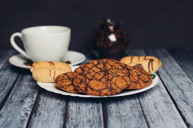 Biscoitos em um prato uma xícara de chá em uma mesa de madeira um lanche