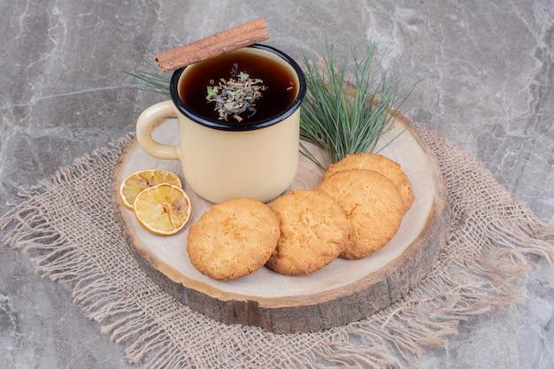 Biscoitos em uma placa de madeira com rodelas de limão e uma xícara de glintwine
