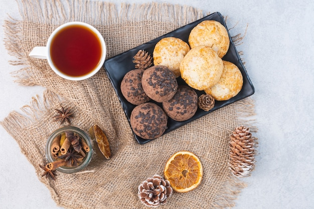 Biscoitos em uma travessa ao lado de uma xícara de chá sobre uma serapilheira, no mármore.
