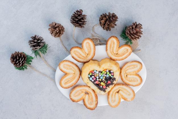 Biscoitos escamosos e um pequeno bolo em uma travessa ao lado de pinhas na mesa de mármore.