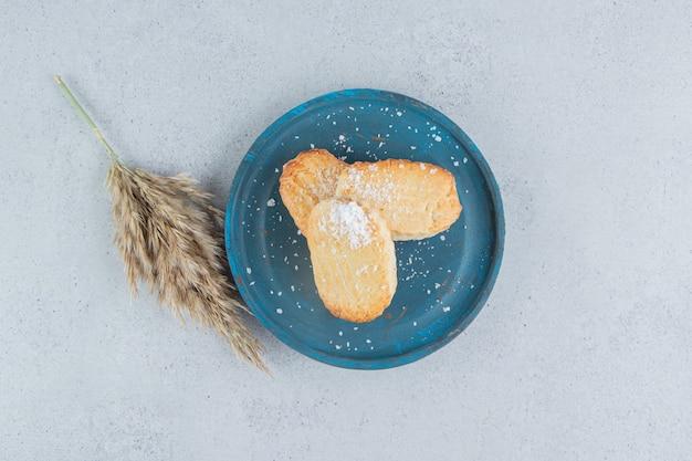 Biscoitos escamosos em uma bandeja azul ao lado de um talo de grama no fundo de mármore.