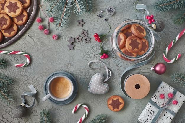 Biscoitos estrelas de natal em fundo verde rústico com galhos de pinheiro e decorações de natal