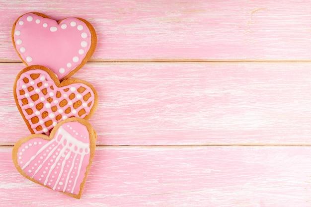 Biscoitos feitos à mão em forma de coração no fundo rosa de madeira para dia dos namorados