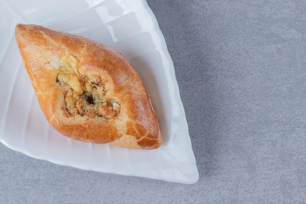 Biscoitos feitos à mão em um prato branco sobre uma superfície cinza