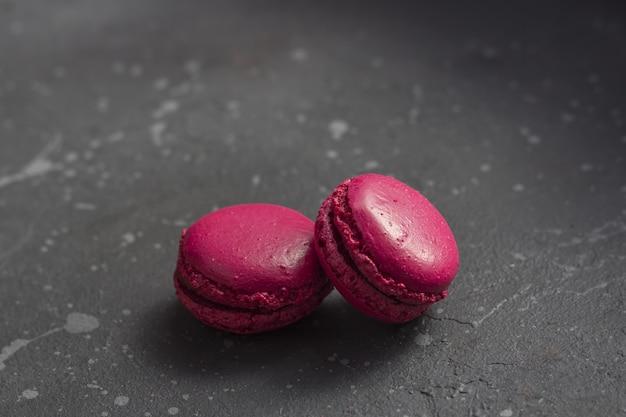 Biscoitos franceses coloridos dos macarons (bolinhos de amêndoa) em um fundo escuro com espaço da cópia. /// tags deve estar em inglês ////