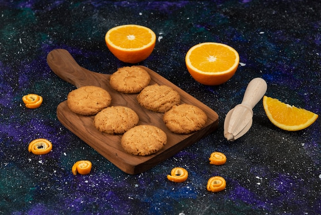 Biscoitos frescos caseiros na tábua de madeira e laranjas cortadas pela metade.