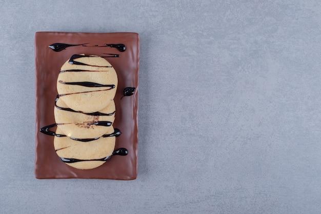 Biscoitos frescos com calda de chocolate no prato marrom