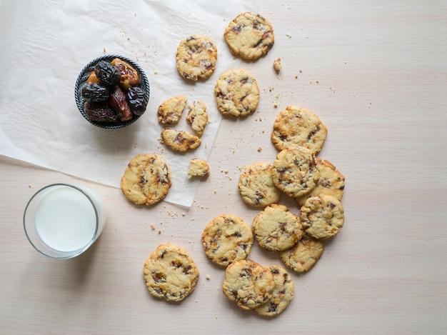 Biscoitos frescos de data suculenta com leite numa superfície de madeira clara