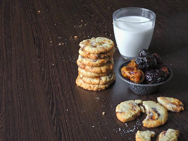 Biscoitos frescos de data suculenta com leite numa superfície de madeira escura
