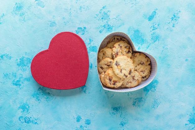 Biscoitos frescos de data suculenta em uma caixa em forma de coração