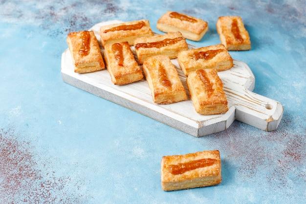 Biscoitos frescos deliciosos com geleia por cima.
