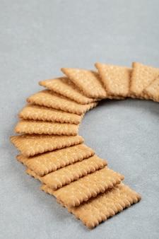 Biscoitos frescos deliciosos em uma superfície cinza.