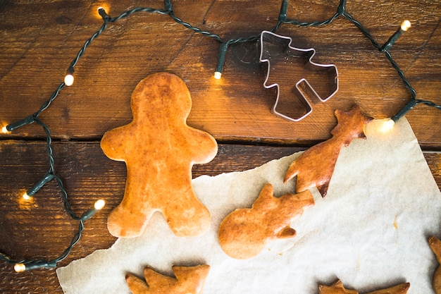 Biscoitos frescos perto de formulário para cookie e luzes de fada